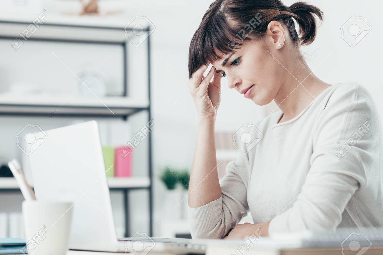Sad tired woman having a bad headache, she is sitting at office desk and touching her temple Stock Photo - 52944800