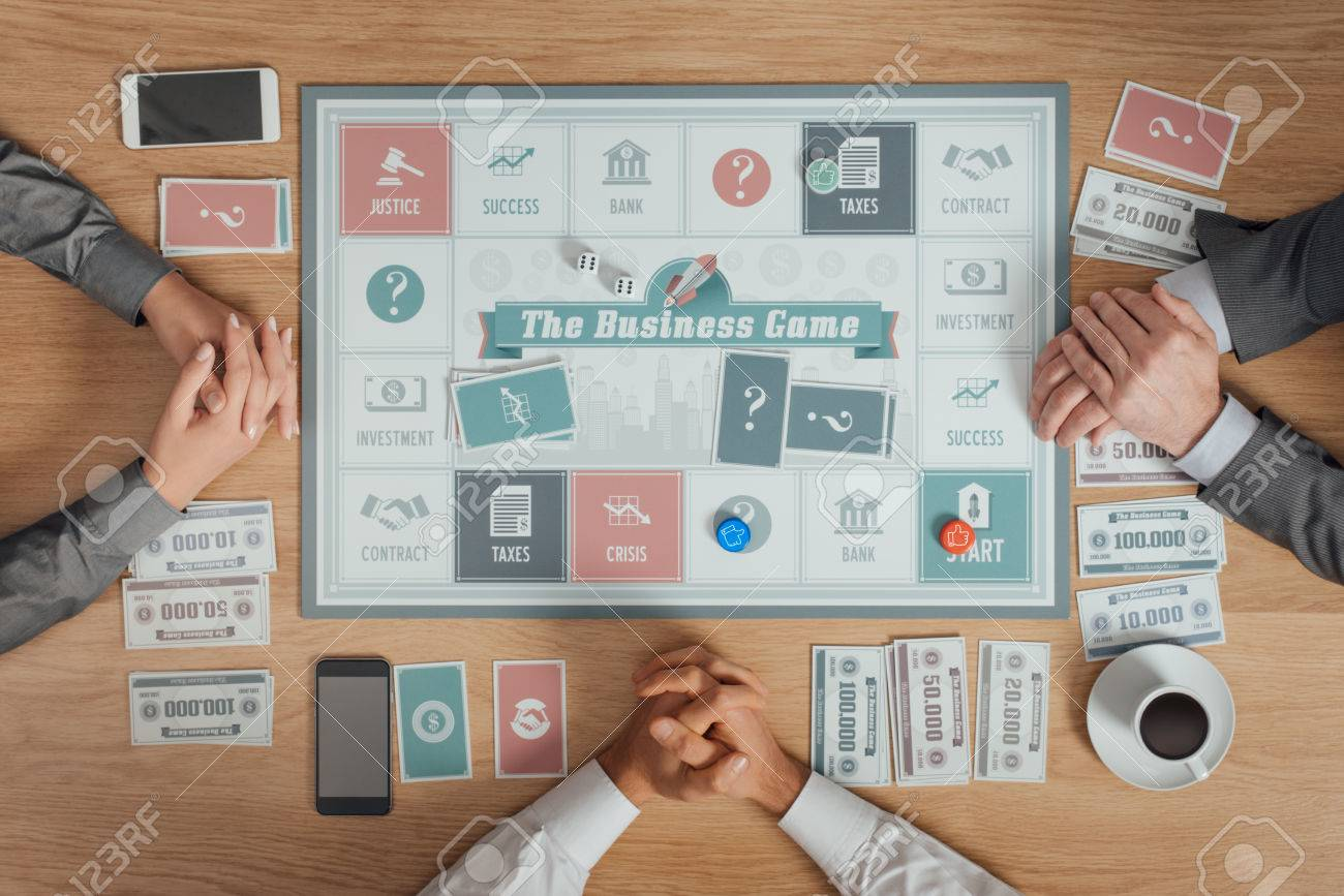 People Playing A Business Board Game On A Wooden Table, They Are Waiting  With Clasped