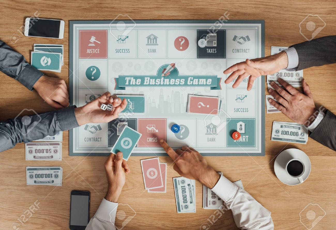 People Playing A Business Board Game On A Wooden Table, Rolling Dices And  Holding Cards
