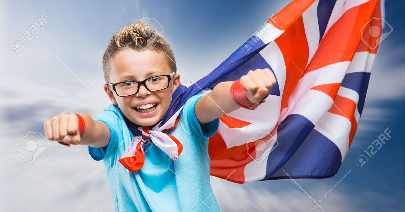 Smiling British super hero wearing a flag as a cape and flying with raised fists Banque d'images - 54081124