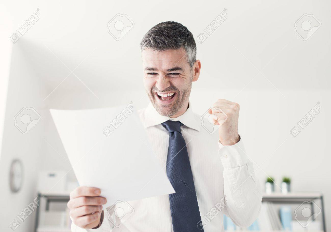 Cheerful businessman in the office receiving good news, he is holding a contract document and raising his fist - 54081685
