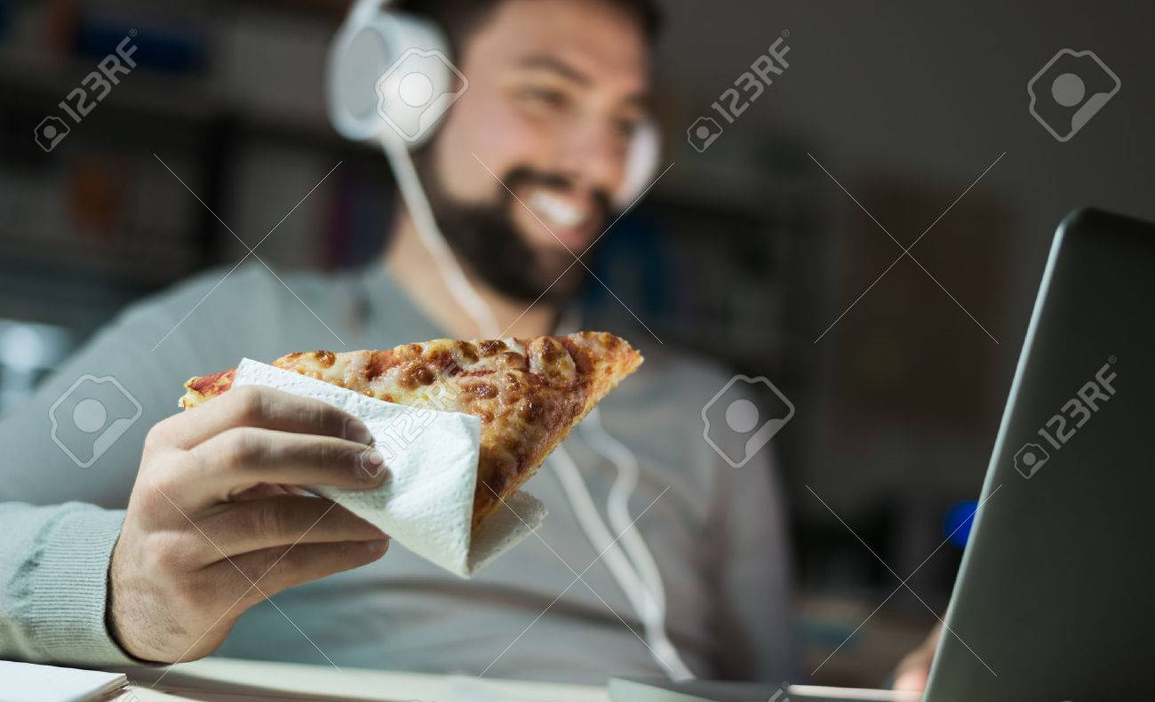 Man at home eating a slice of pizza and social networking with a laptop late at night Banque d'images - 54081579