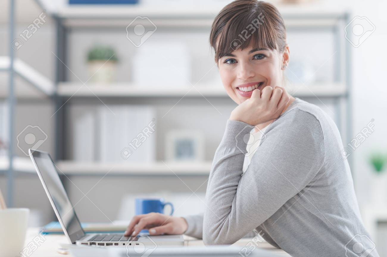 Happy confident businesswoman sitting at office desk and working with a laptop, she is smiling at camera Stock Photo - 61531086