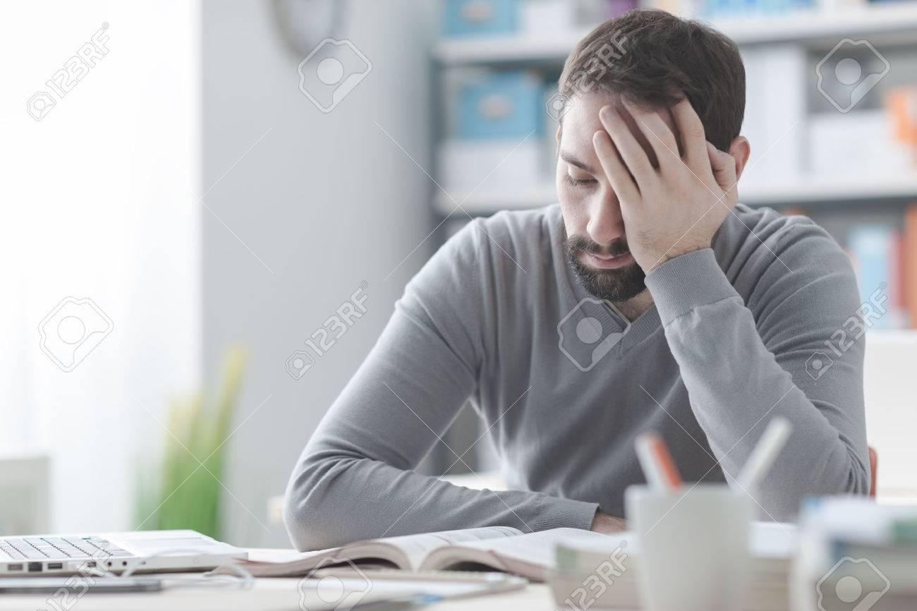 Puisé jeune homme travaillant au bureau et toucher sa tête il a