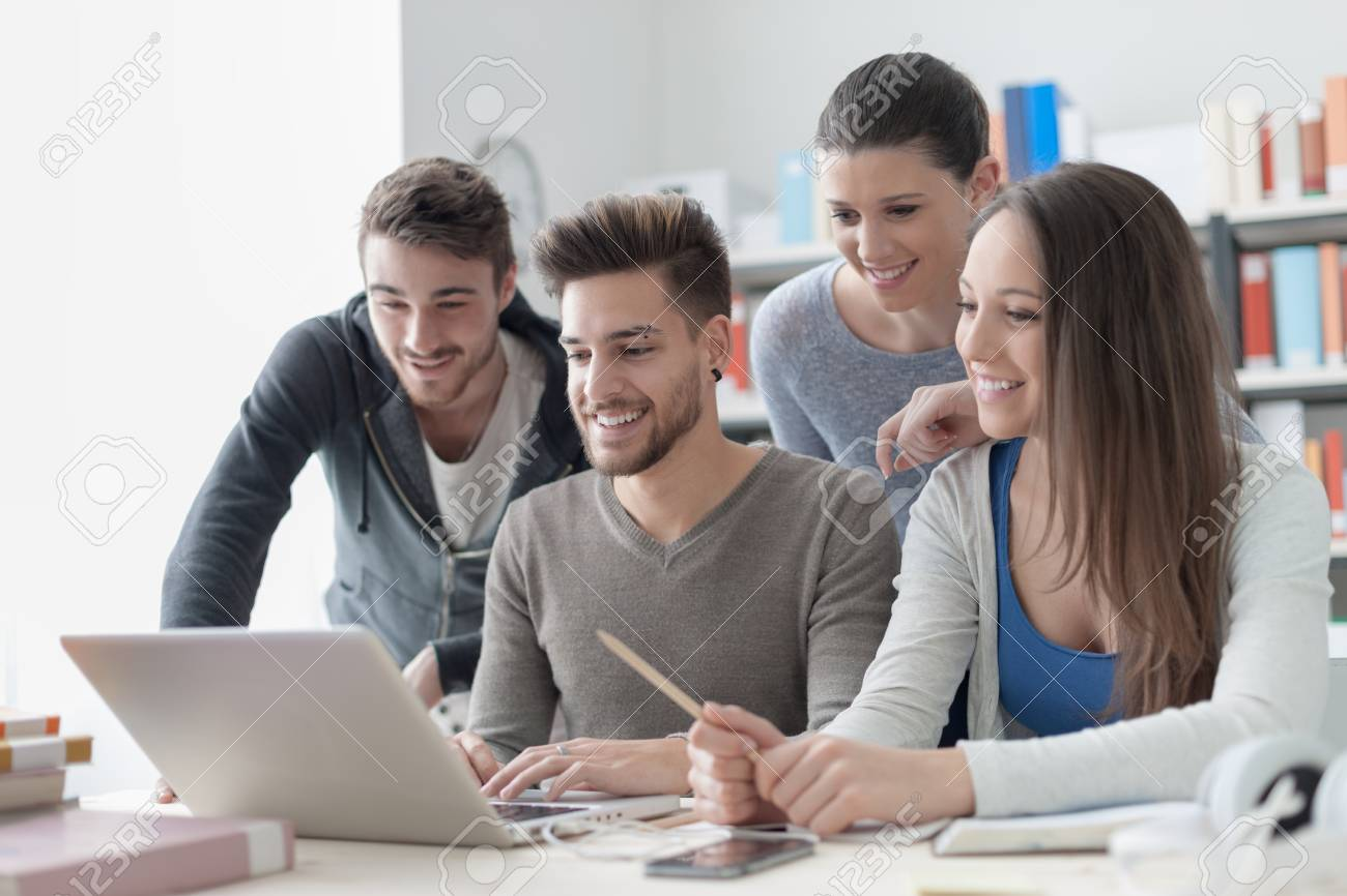 Group Of Smiling College Students Using A Laptop And Studying Stock Photo Picture And Royalty Free Image Image 61891718