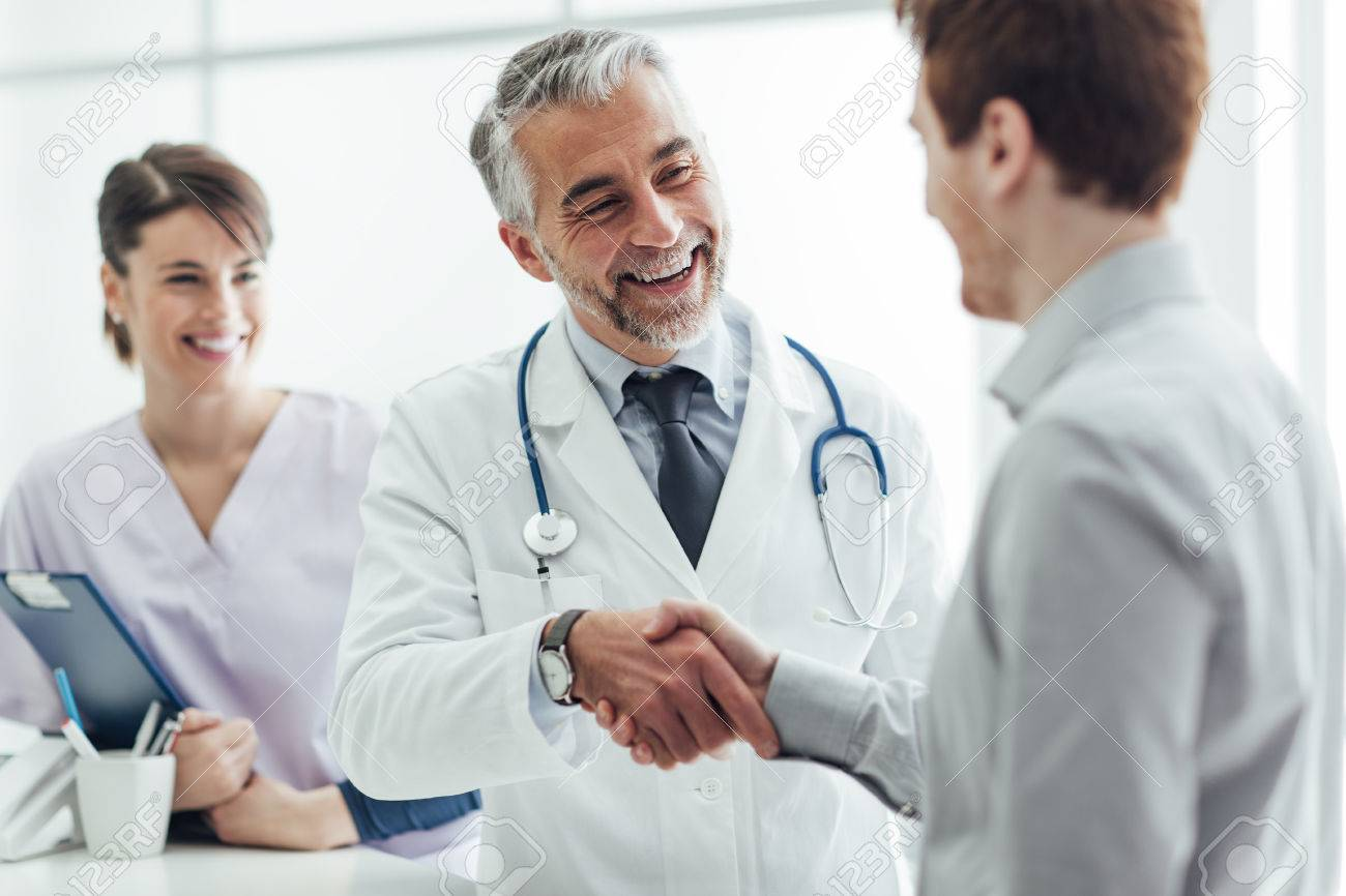 Smiling doctor at the clinic giving an handshake to his patient, healthcare and professionalism concept Stock Photo - 62025951
