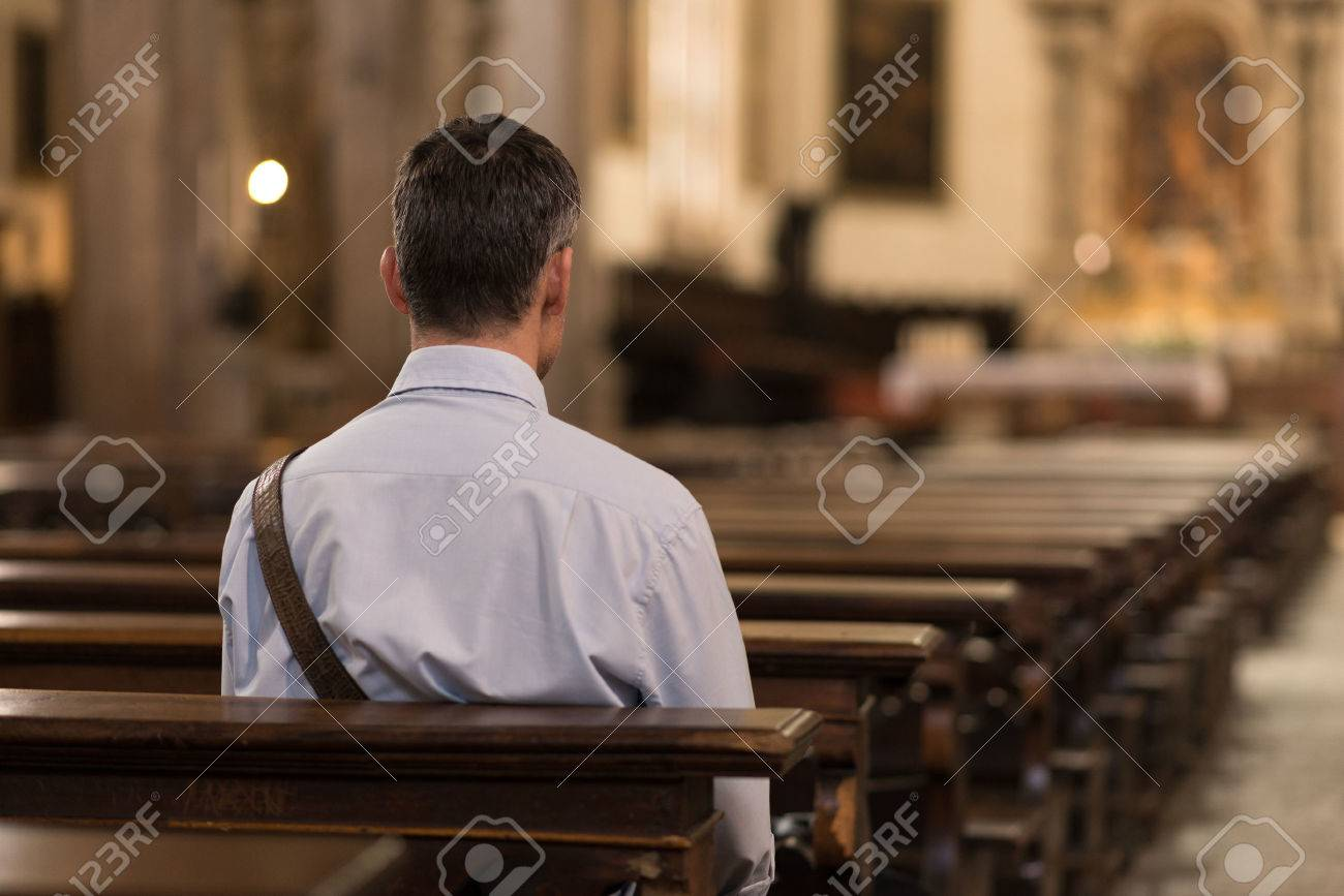 Man sitting in a pew at Church and meditating Banque d'images - 63230179