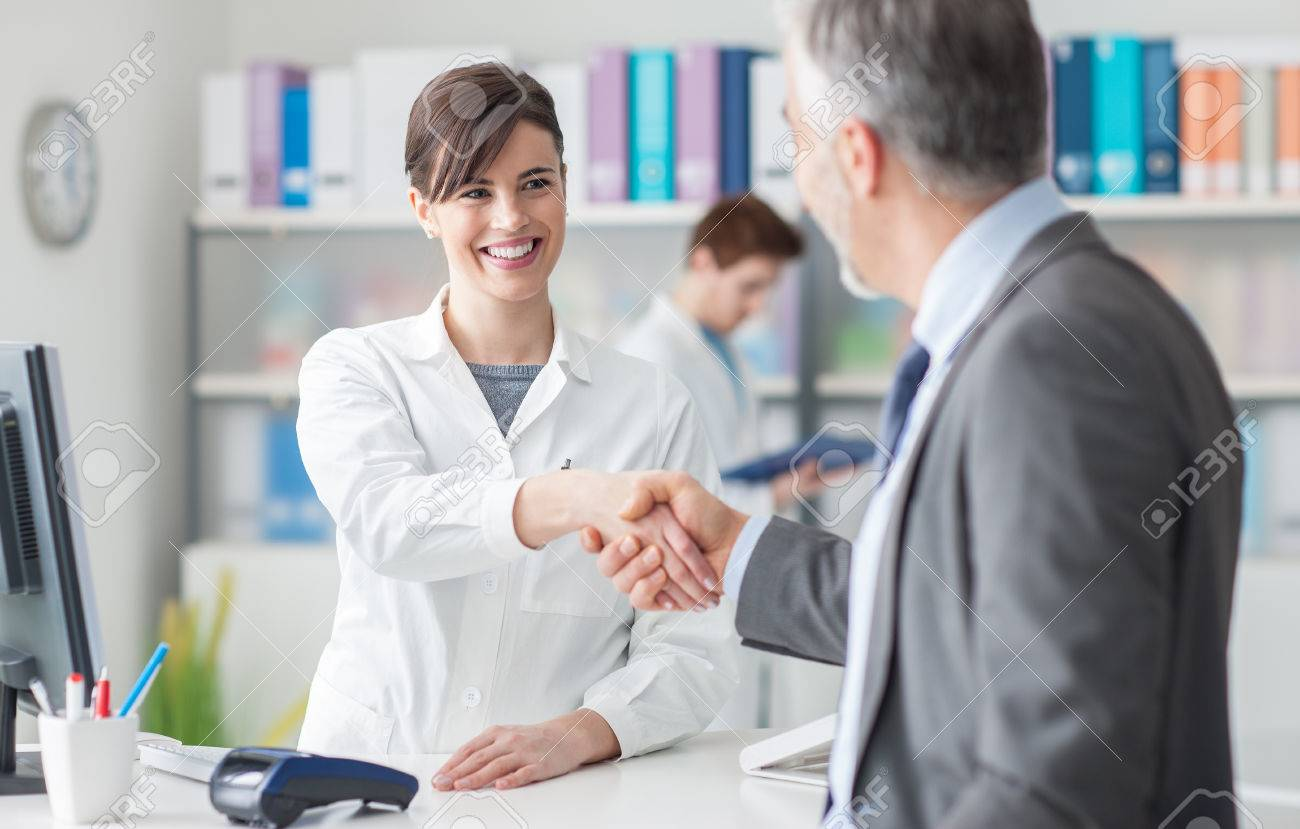Patient shaking hands with a female doctor at the clinic reception, healthcare and customer satisfaction concept Stock Photo - 63503235