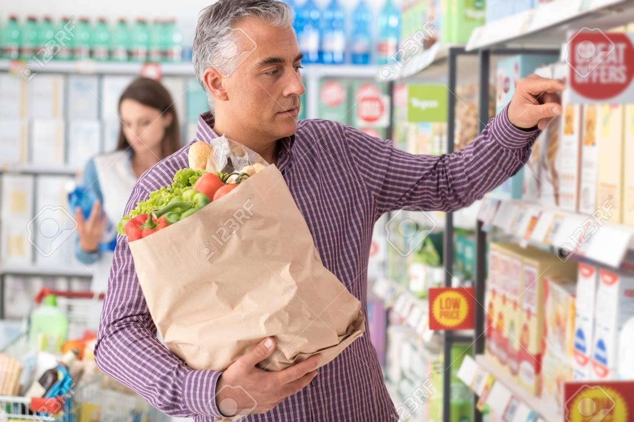 El hombre que hace las compras de comestibles en el supermercado, él está buscando productos en el estante de la tienda y la celebración de una bolsa