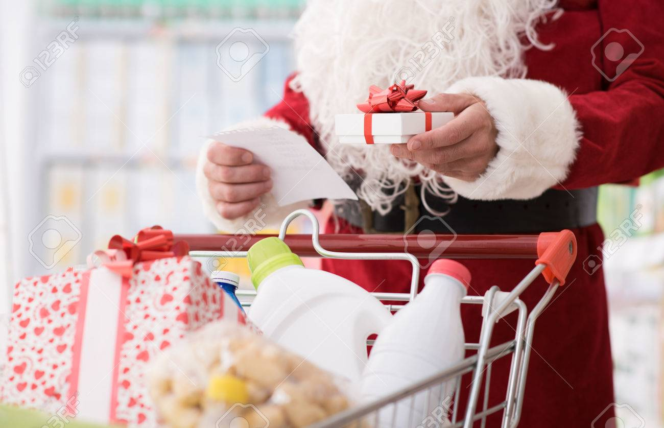 Santa Claus doing grocery shopping at the supermarket, he is pushing a full cart and checking a list, Christmas and shopping concept - 67277889