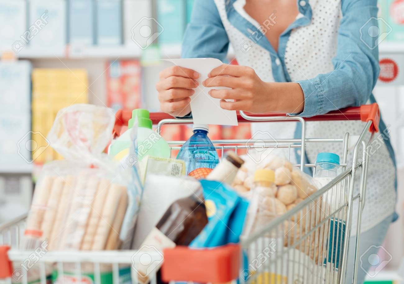 Woman doing grocery shopping at the supermarket, she is pushing a cart and checking a list - 67274438