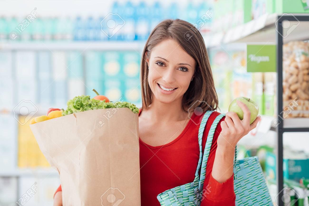Sonriente mujer joven de compras en el supermercado, ella está sosteniendo una bolsa de supermercado con verduras orgánicas frescas
