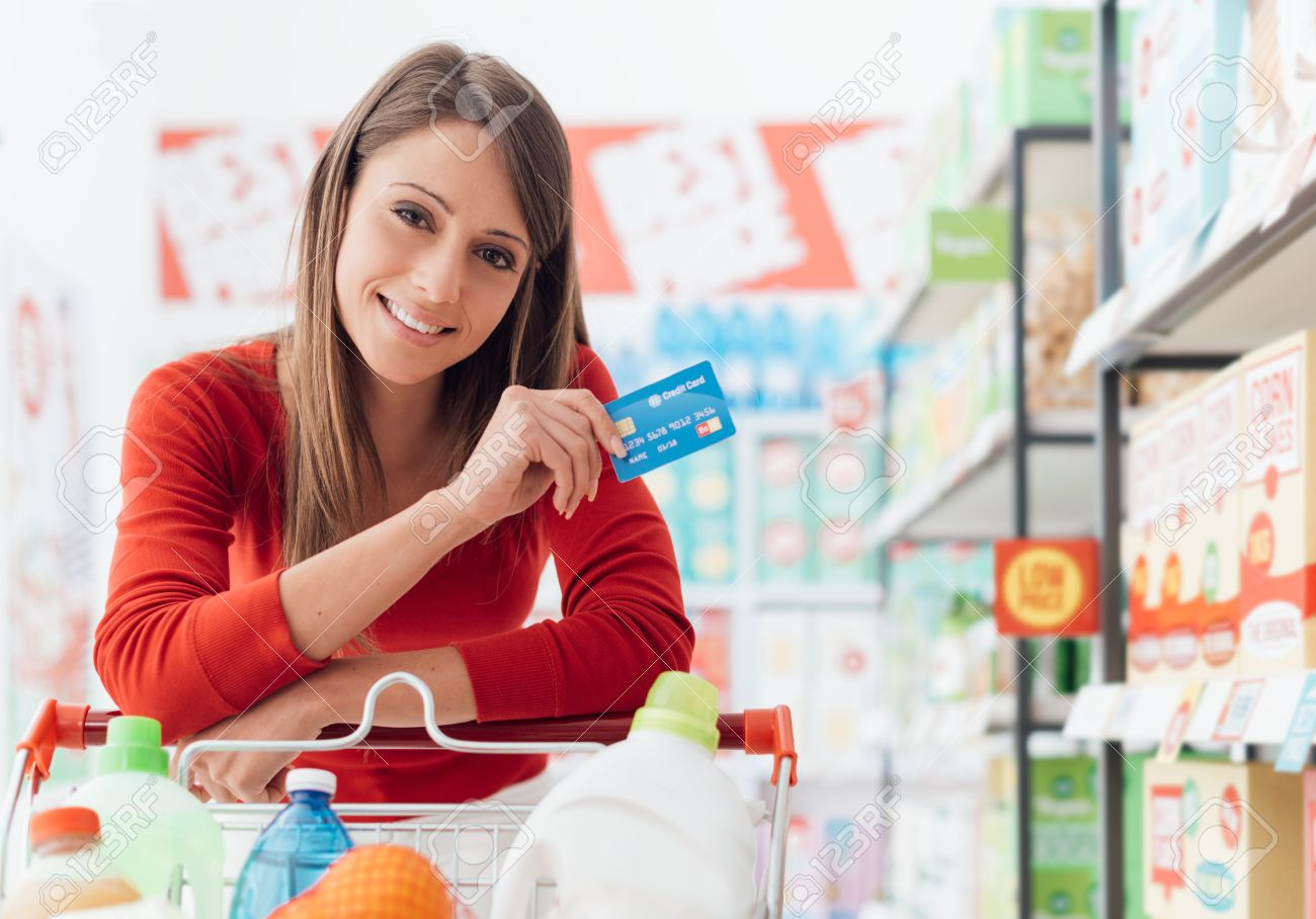 Smiling woman doing grocery shopping at the supermarket she is leaning on a full cart and holding a credit card - 67399024