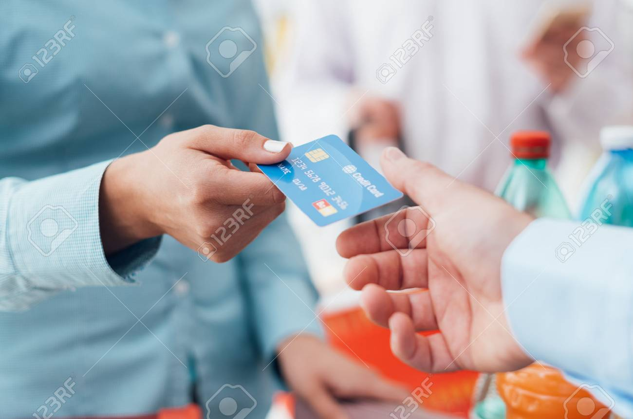 Woman at the supermarket checkout, she is giving her credit card to the cashier, retail and payments concept - 67220940
