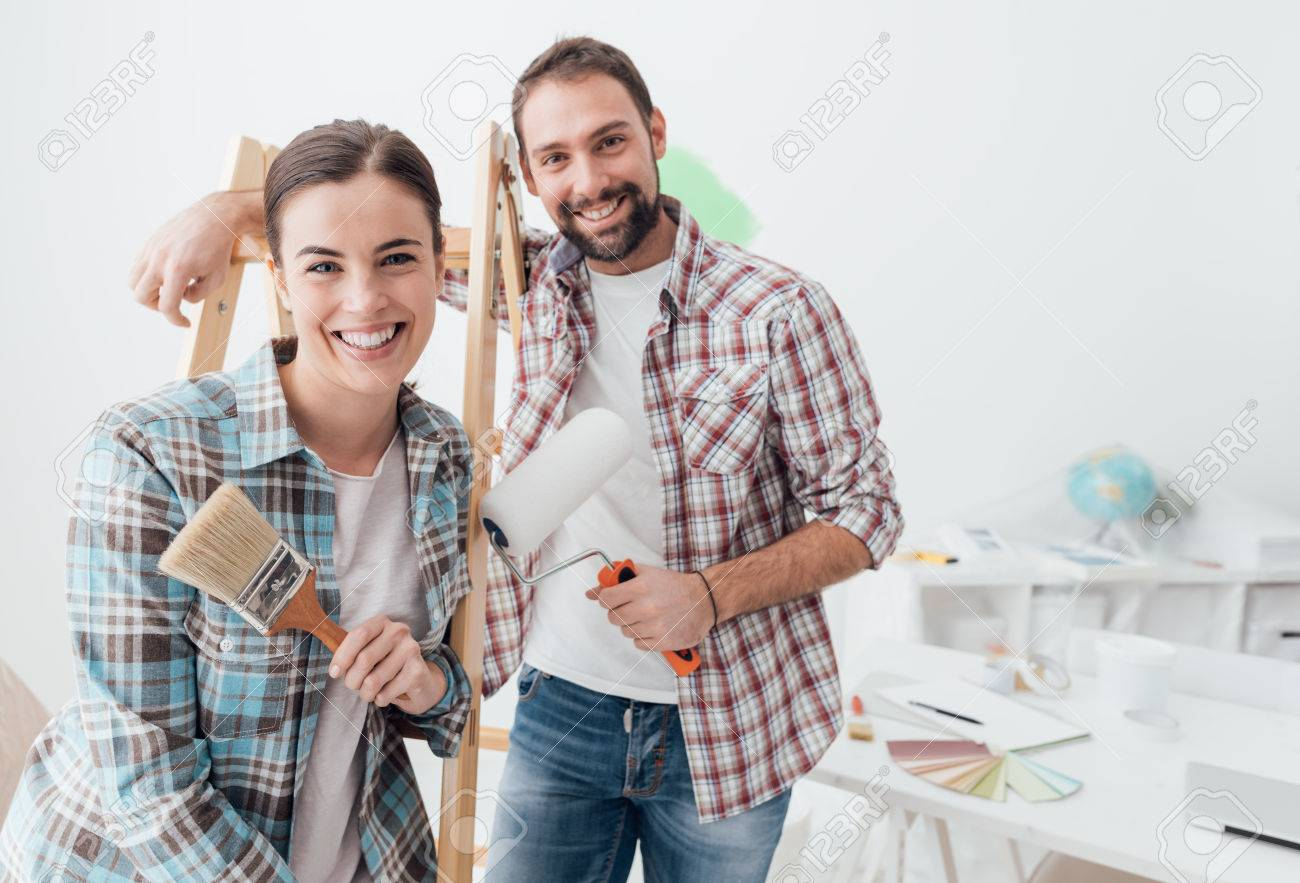 Creative young couple renovating their house and painting walls, they are posing together and smiling at camera - 71999223