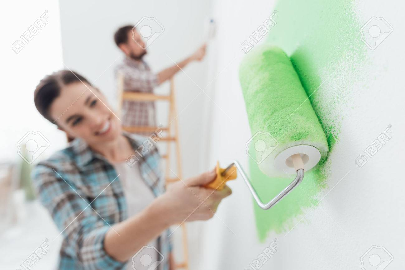 Happy couple painting walls in their new house: the man is standing on a ladder and the woman is using a paint roller and applying bright green paint - 71995690