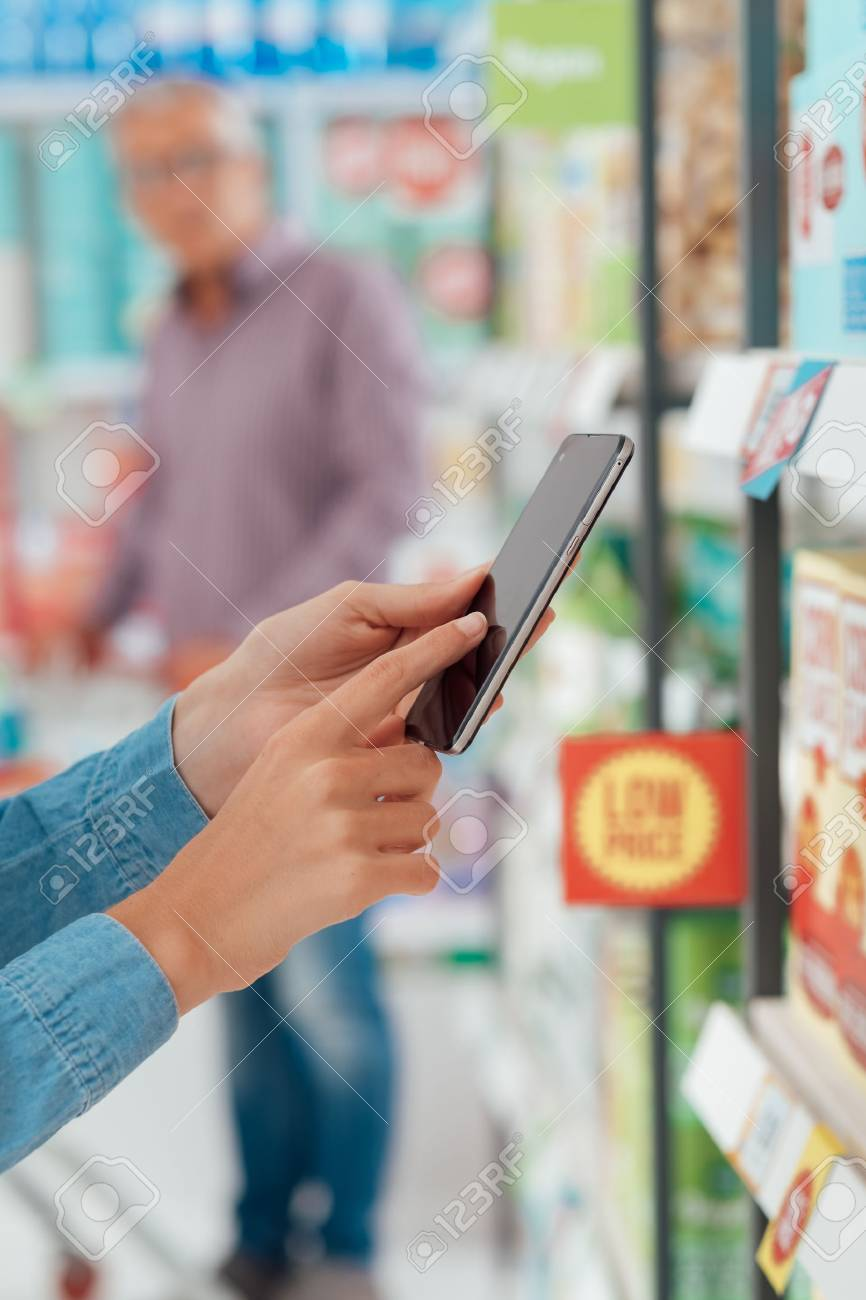 Woman shopping at the supermarket, she is checking products and offers using her smart phone, augmented reality and retail concept - 72559445