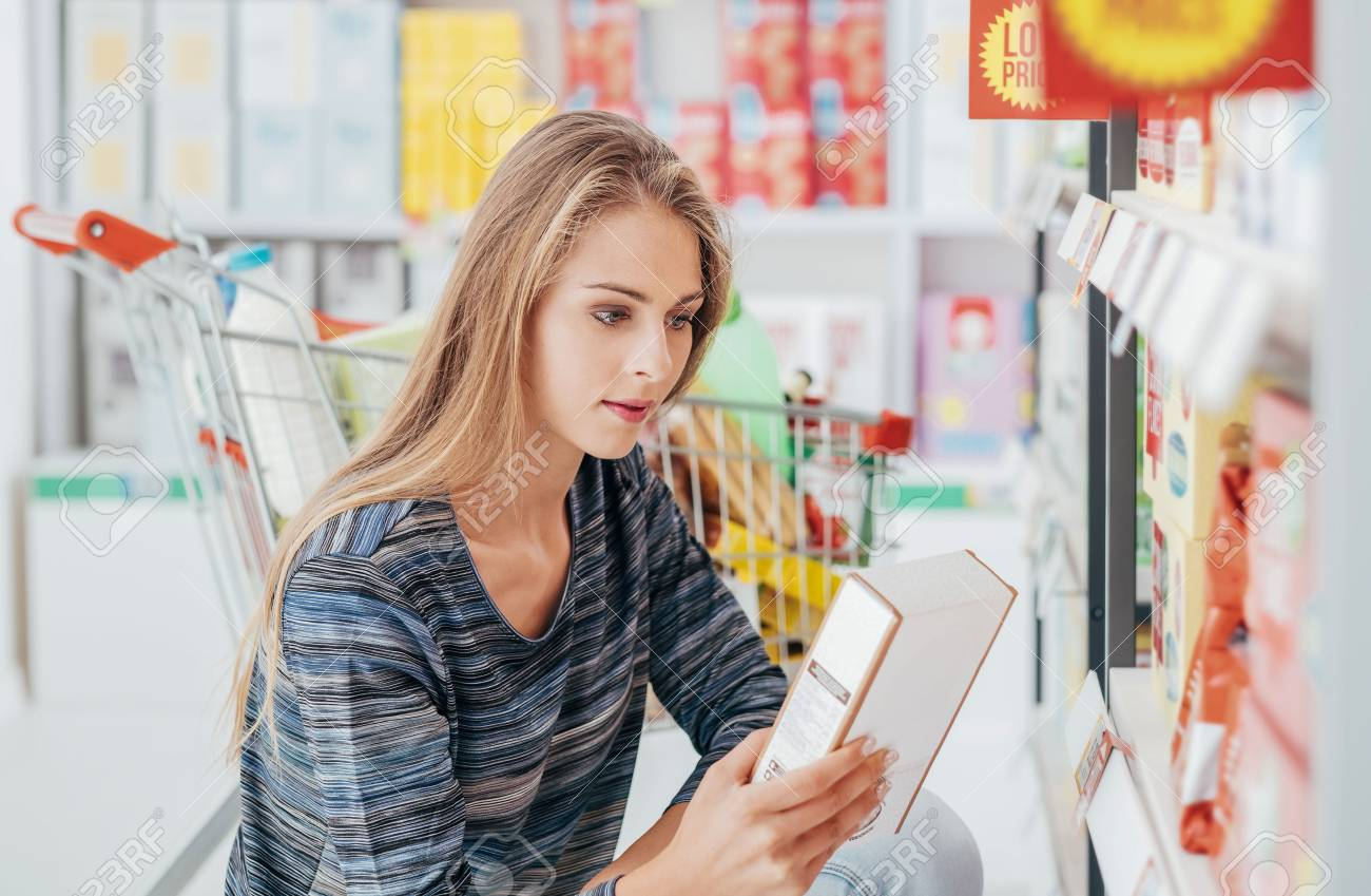 Young woman doing grocery shopping at the supermarket and reading a food label with ingredients on a box, shopping and nutrition concept - 72662622