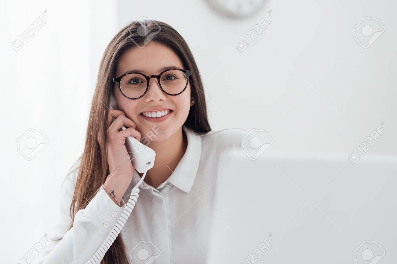 Efficient smiling secretary answering phone calls and talking with customers, she is sitting at desk and working with a laptop - 74391680