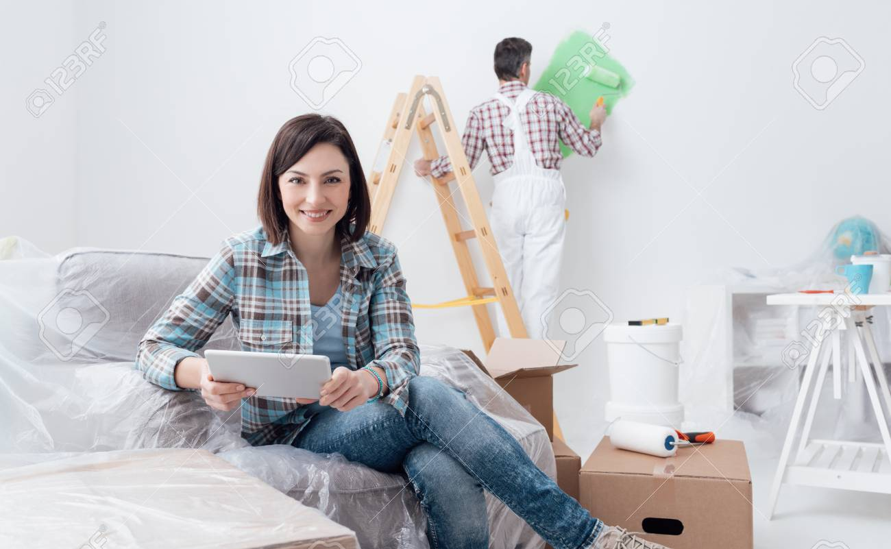 Happy woman relaxing and connecting with her tablet while a painter is painting the room, home renovation concept - 84193058