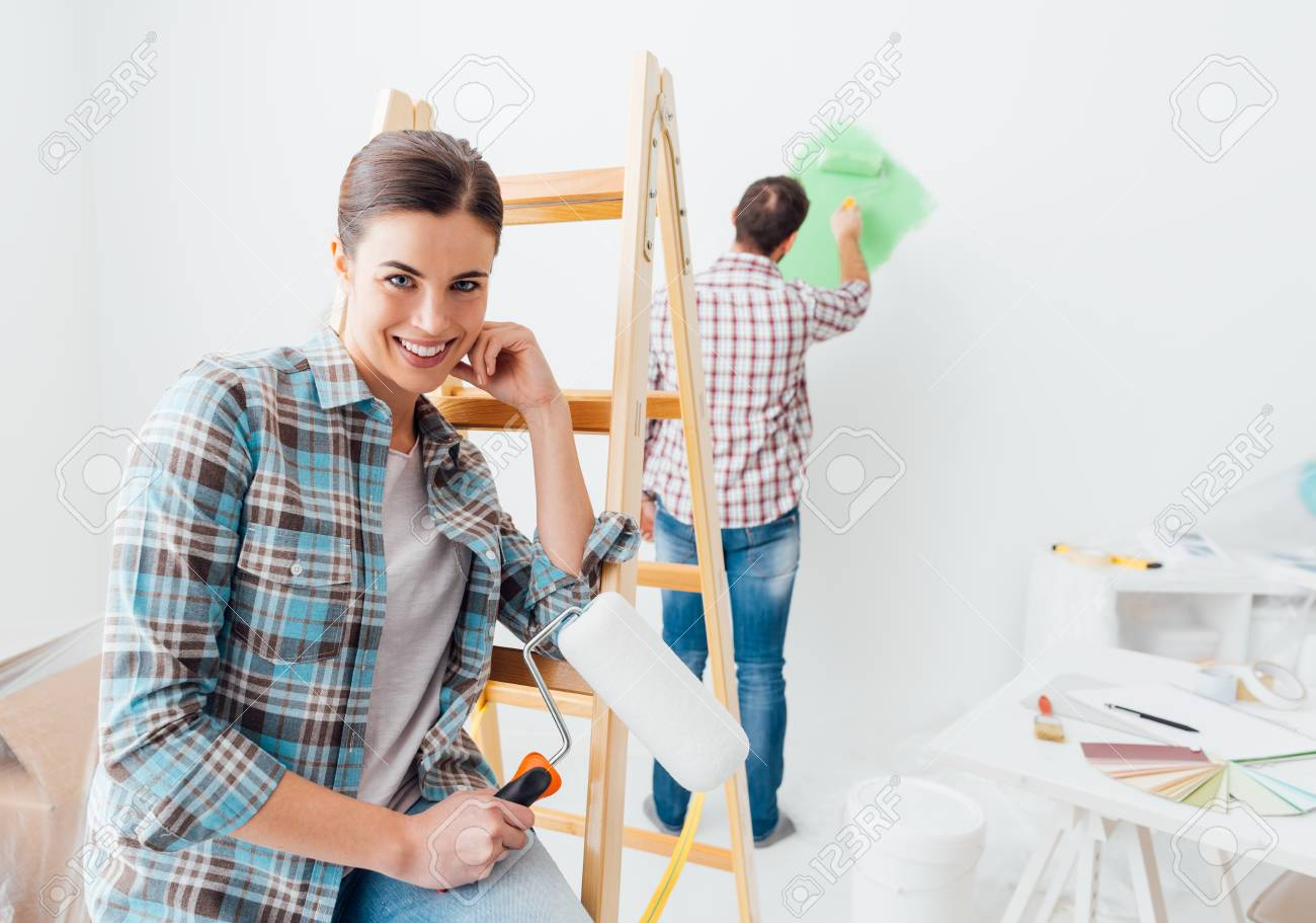 Home makeover and renovation: young couple painting their new