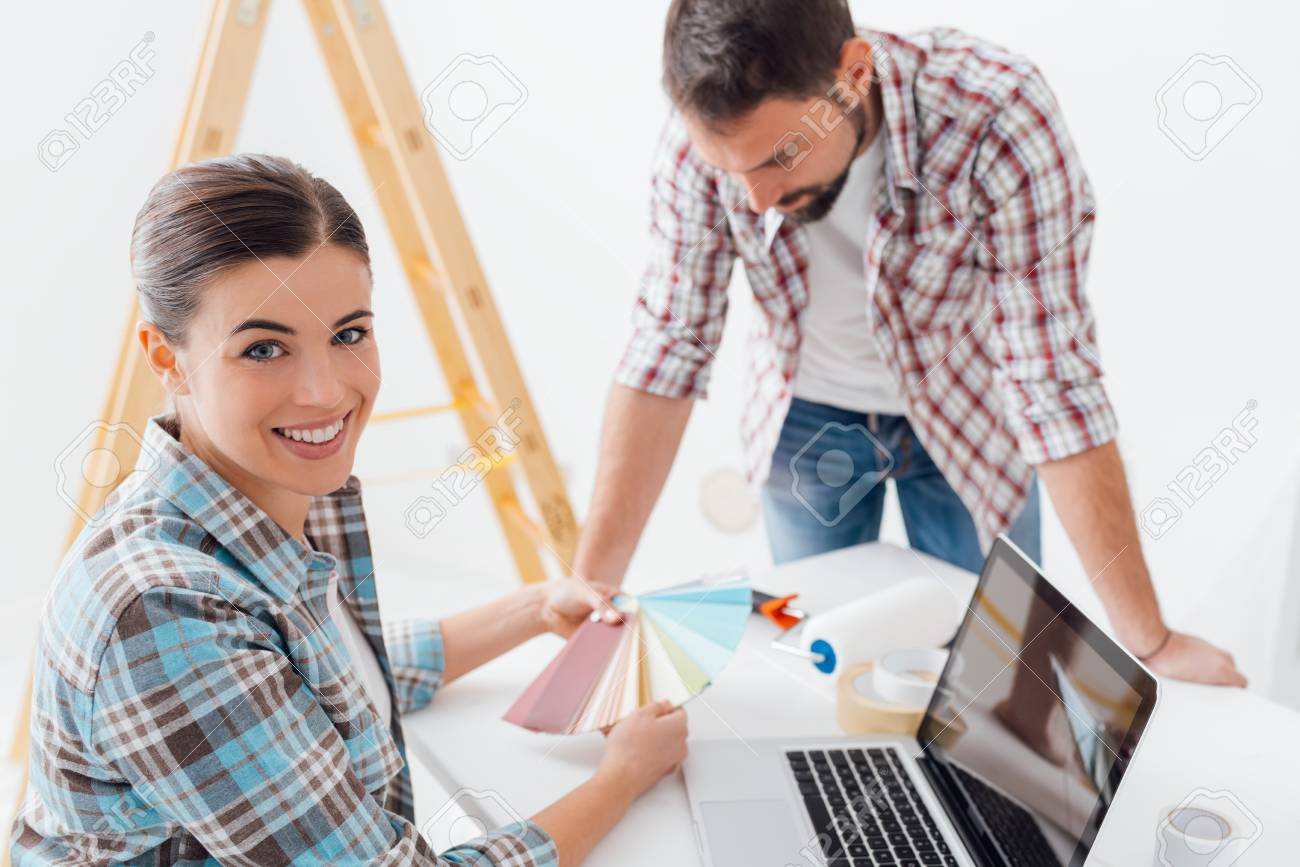 Young smiling couple renovating their home, they are choosing paint color swatches together - 84137796