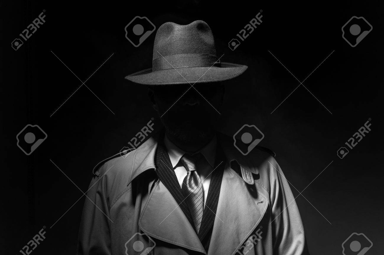 Man posing in the dark with a fedora hat and a trench coat, 1950s noir film style character - 84133717