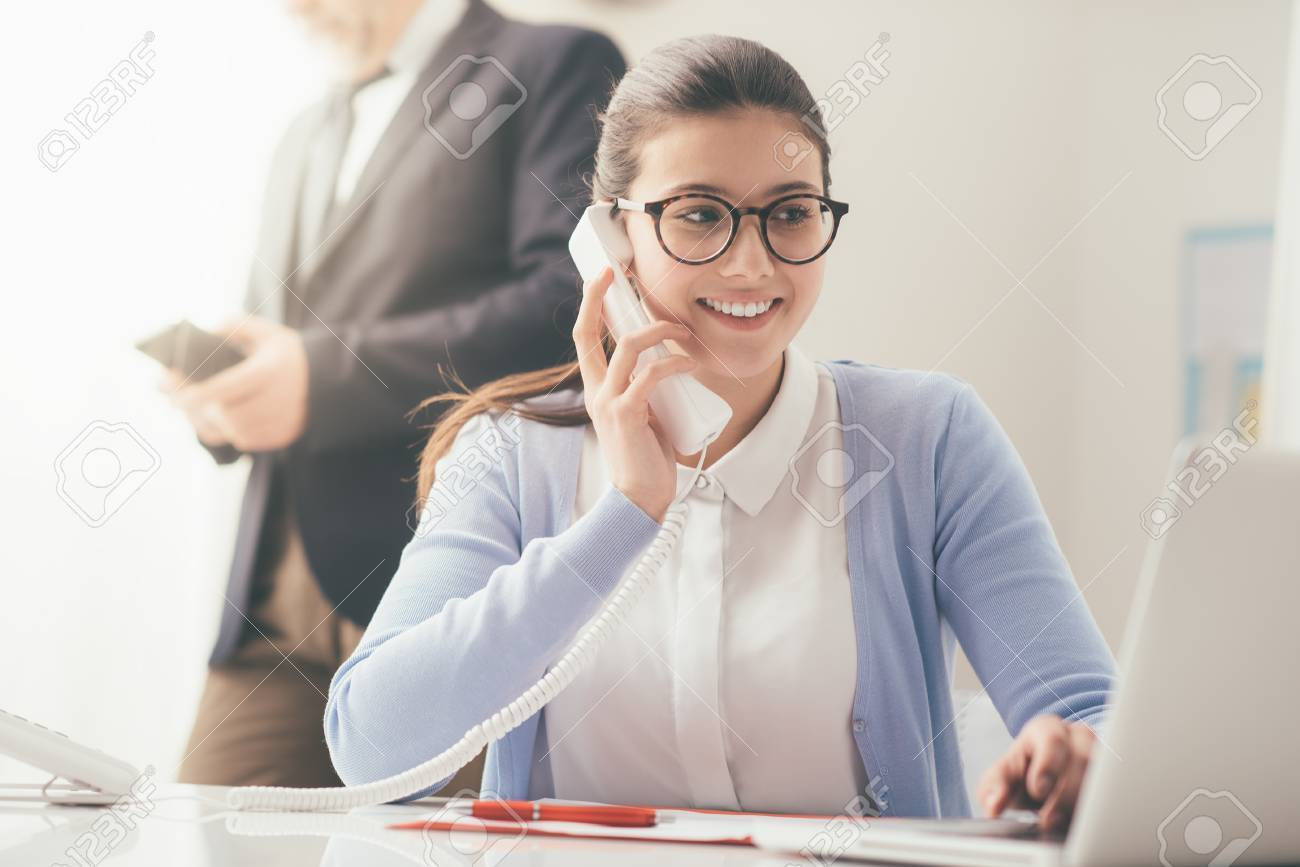Efficient smiling secretary answering phone calls and talking with customers, she is sitting at desk and working with a laptop - 84116153