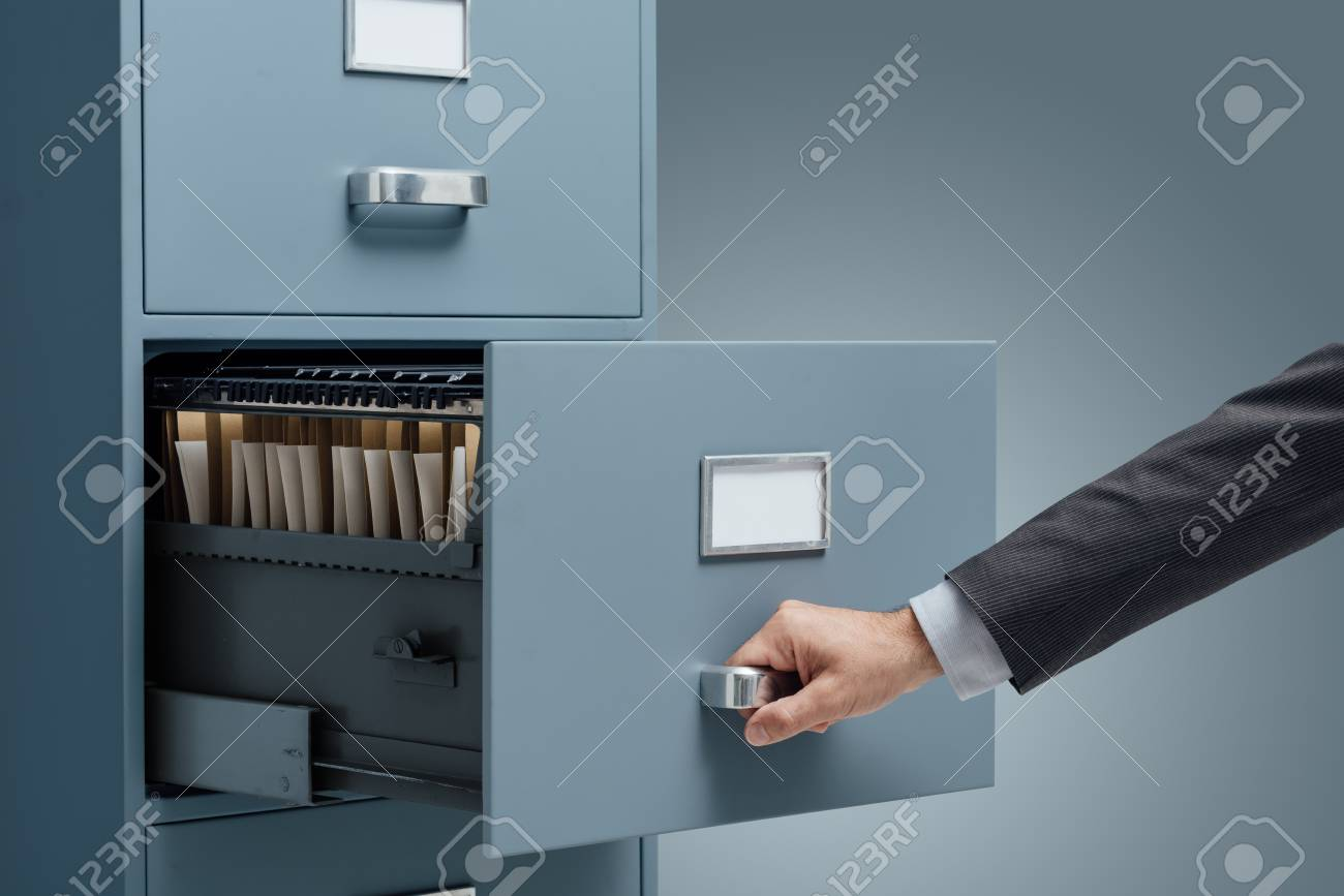 Office clerk searching files in a filing cabinet, data storage and administration concept - 88211712