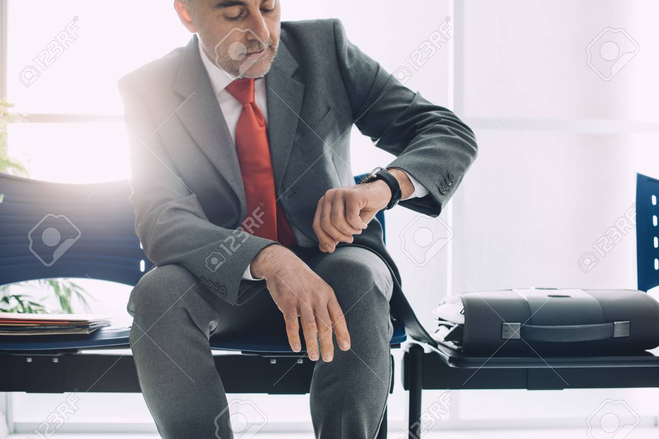 Corporate businessman sitting in the waiting room and checking the time, he is waiting for the meeting - 89095560