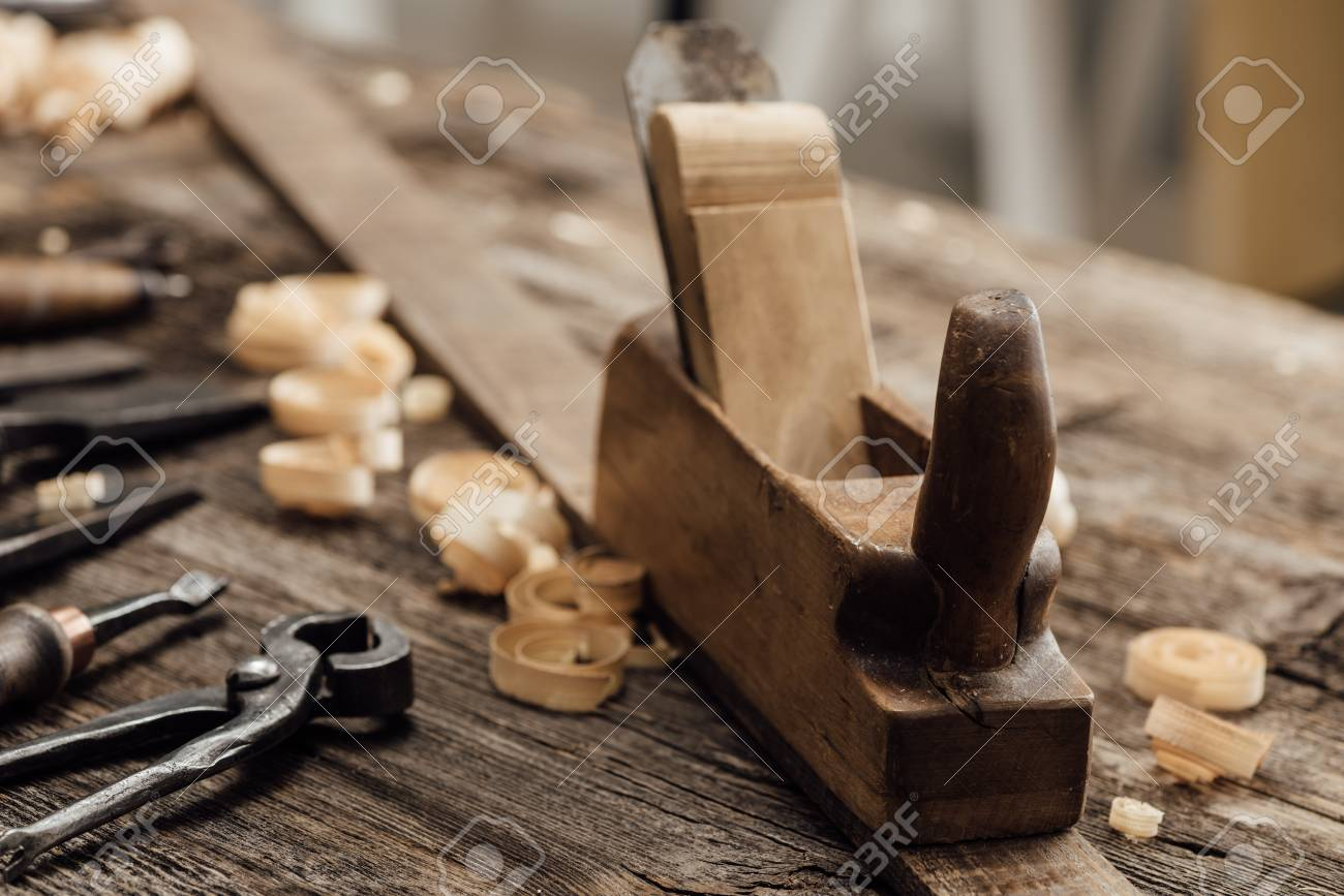 Wood planer on the carpenter's workbench and old woodworking tools, carpentry and do it yourself concept - 89418224