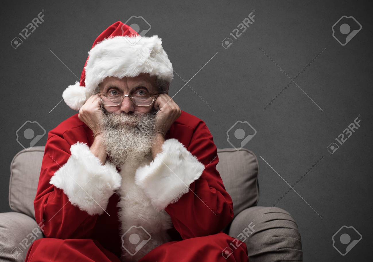 Santa Claus sitting on the armchair and waiting for Christmas, he is resting his head on his hands - 89097219
