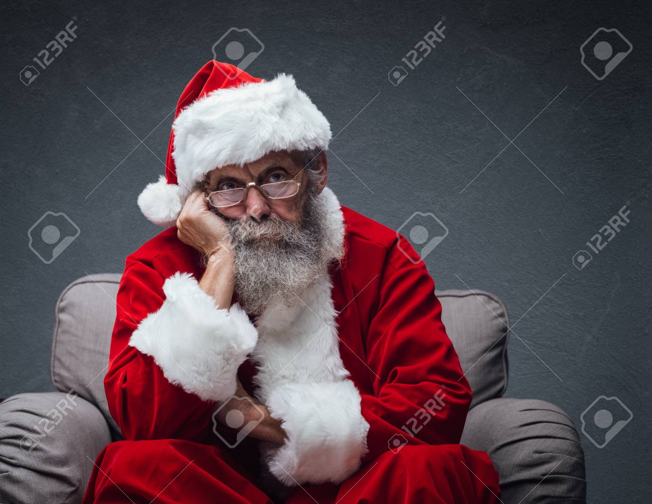 Lazy bored Santa Claus leaning on his hand and relaxing on the armchair, he is waiting for Christmas - 89097221