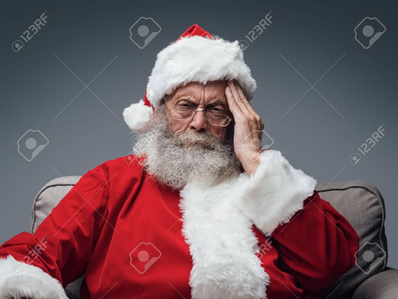 Sad Santa Claus having an headache on Chistmas Eve, stress and illness concept - 89097284