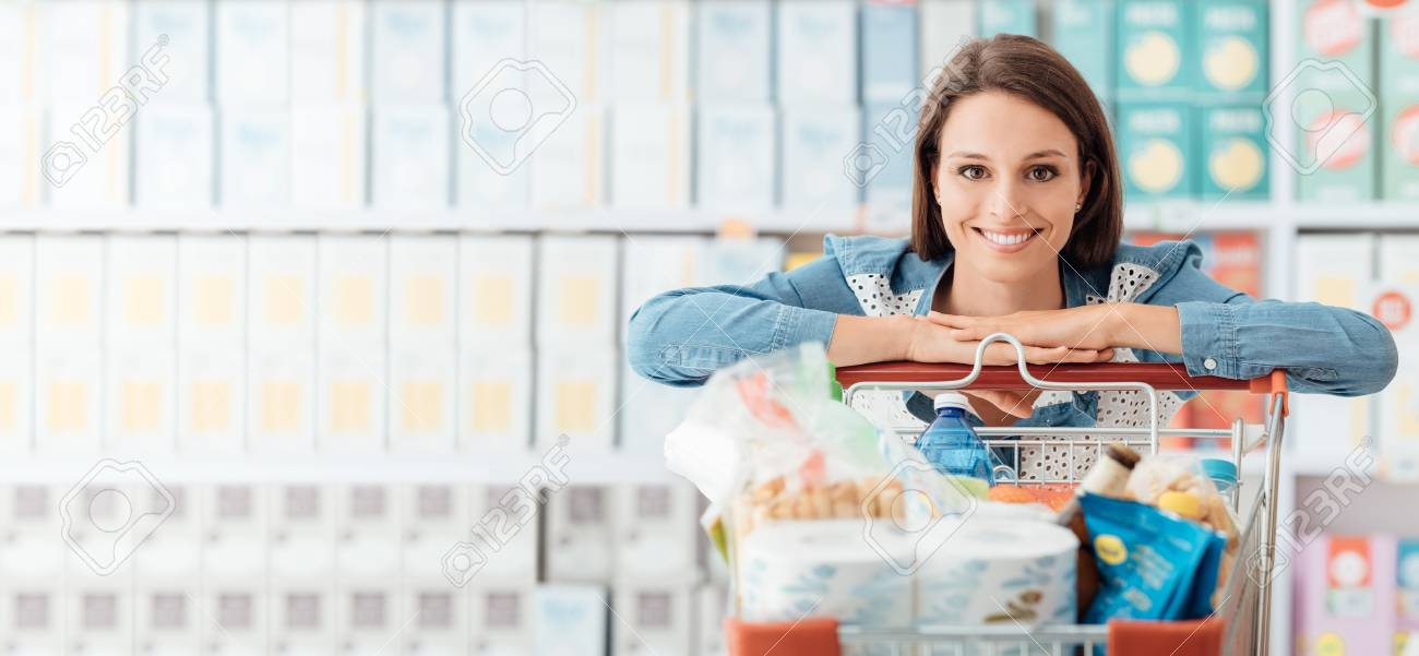 Smiling happy woman enjoying shopping at the supermarket, she is leaning on a full cart, lifestyle and retail concept - 90167960
