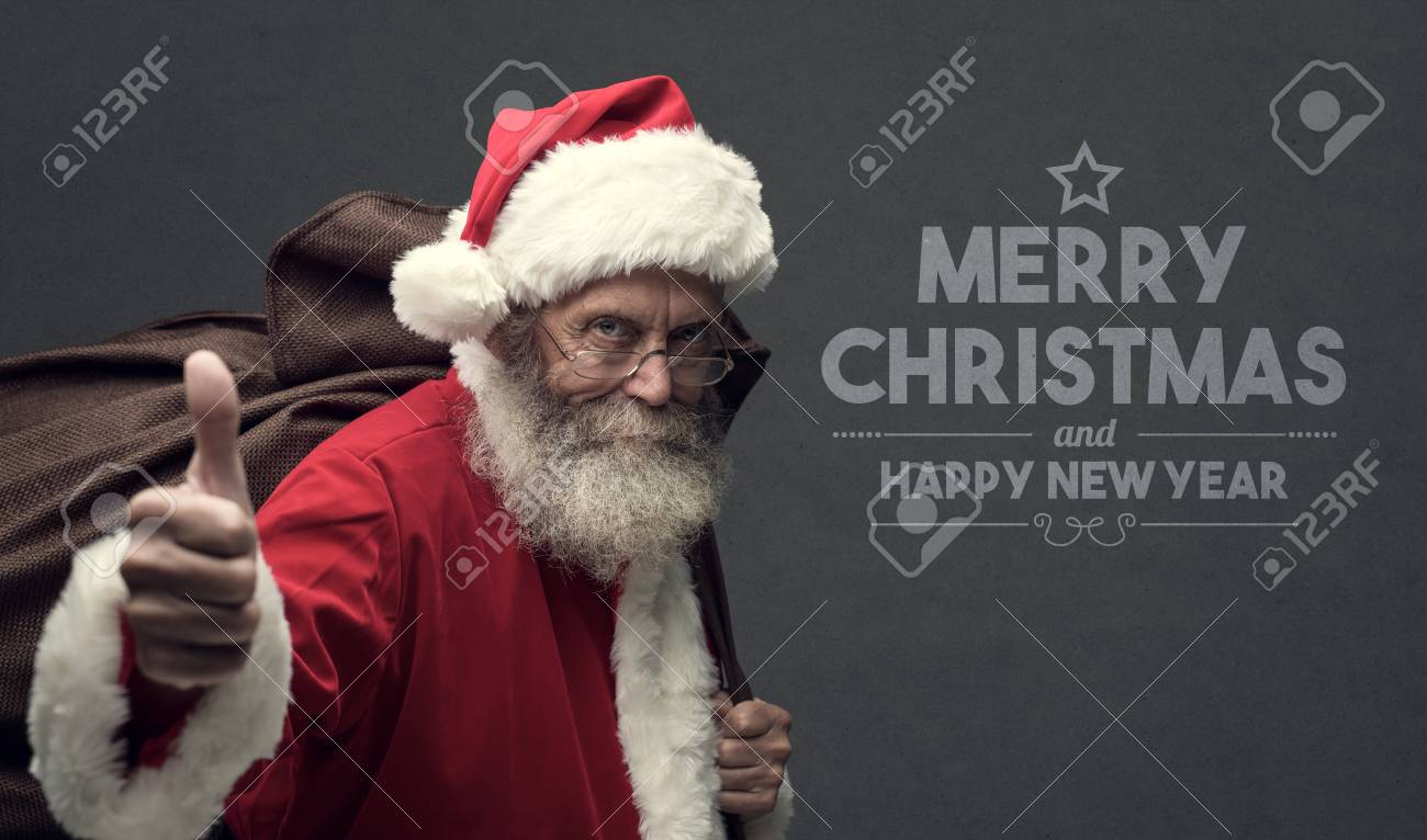 Huge Christmas Card.Confident Happy Santa Claus Giving A Thumbs Up And Carrying Christmas