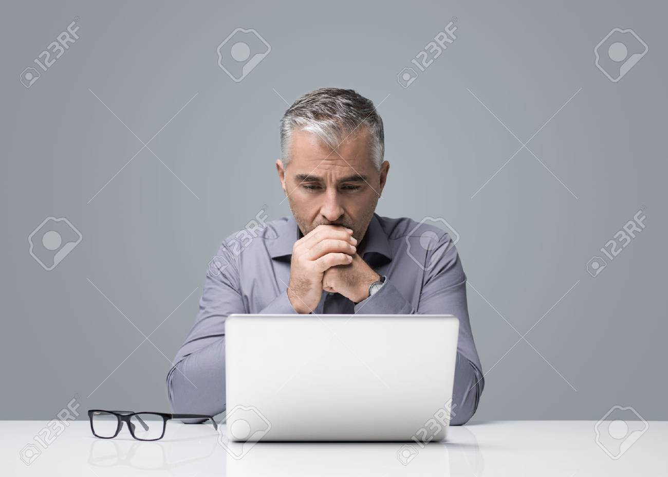 Mature businessman sitting at desk and working with a laptop, he is reading and thinking, business strategies and problem solving concept - 91424987