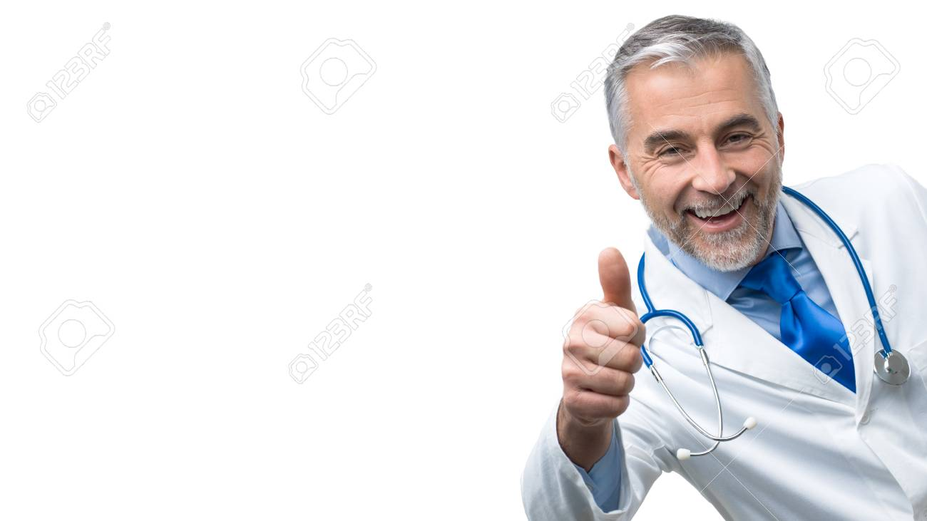 confident smiling mature doctor posing and giving a thumbs up stock