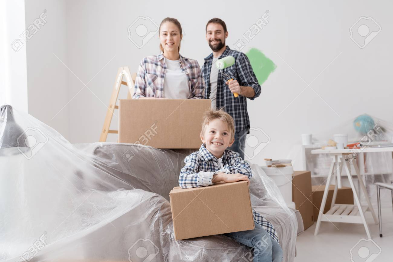 Happy Family Moving In A New House And Painting Rooms They Are Posing Together Stock