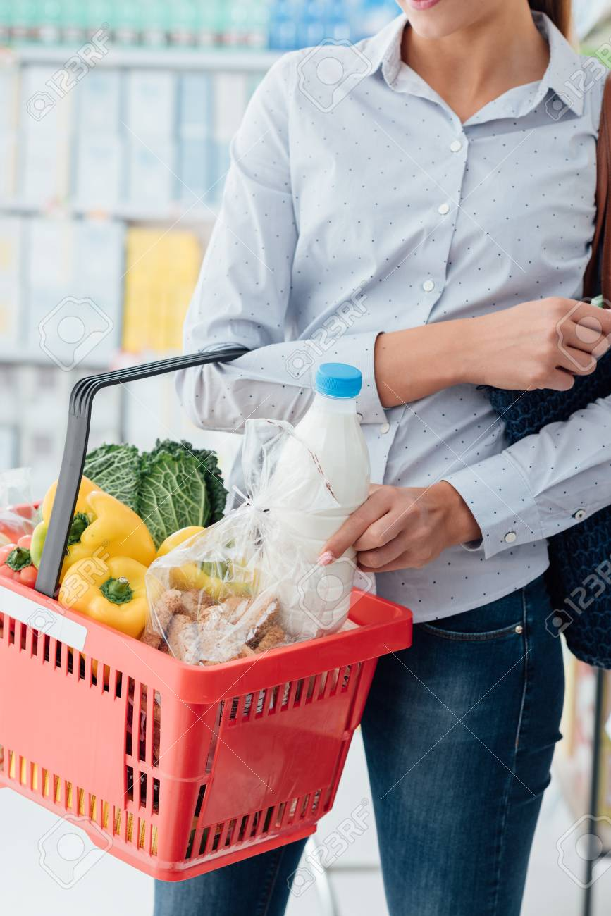 Woman doing grocery shopping at the supermarket, she is putting a bottle of milk into a shopping basket - 96976992