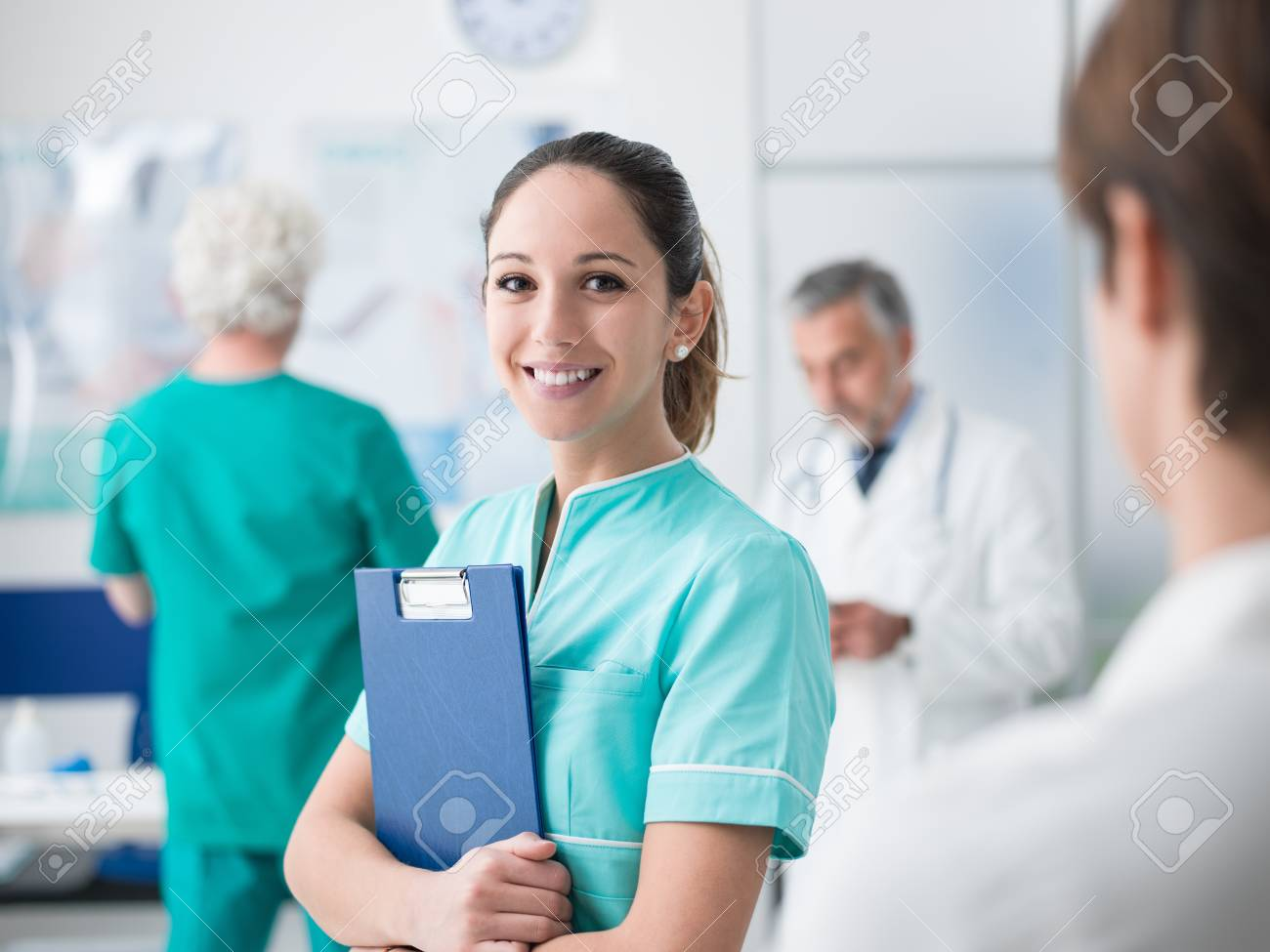 Young female medical student working at the hospital and medical staff, she is holding medical records - 96977320