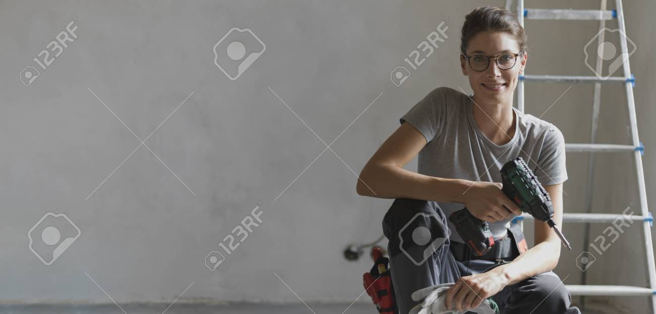 Professional repairwoman with tool belt doing a home renovation, she is posing and holding a drill - 108157682