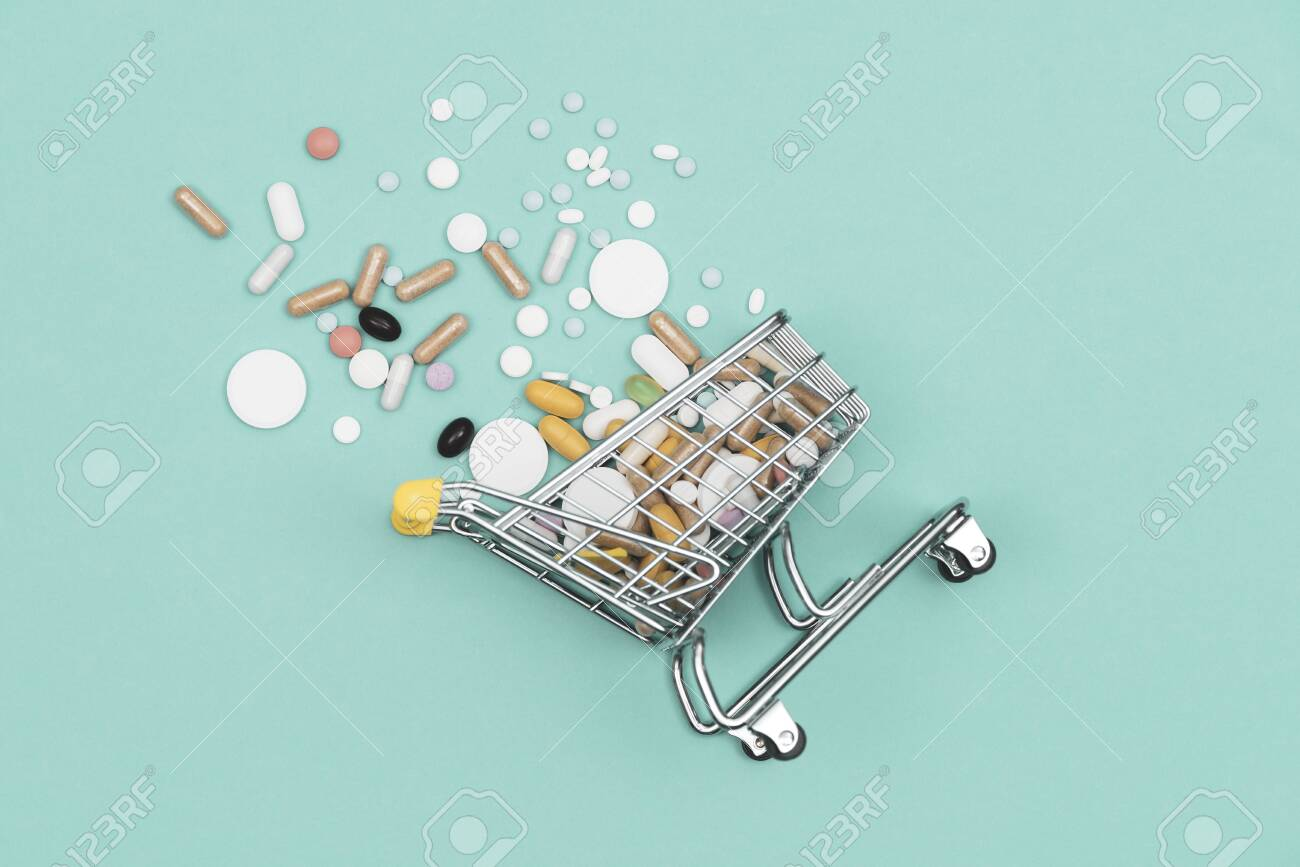 Miniature shopping cart filled with pills, tablets and capsules: pharmacy shopping, medicine and drug abuse concept - 121245408