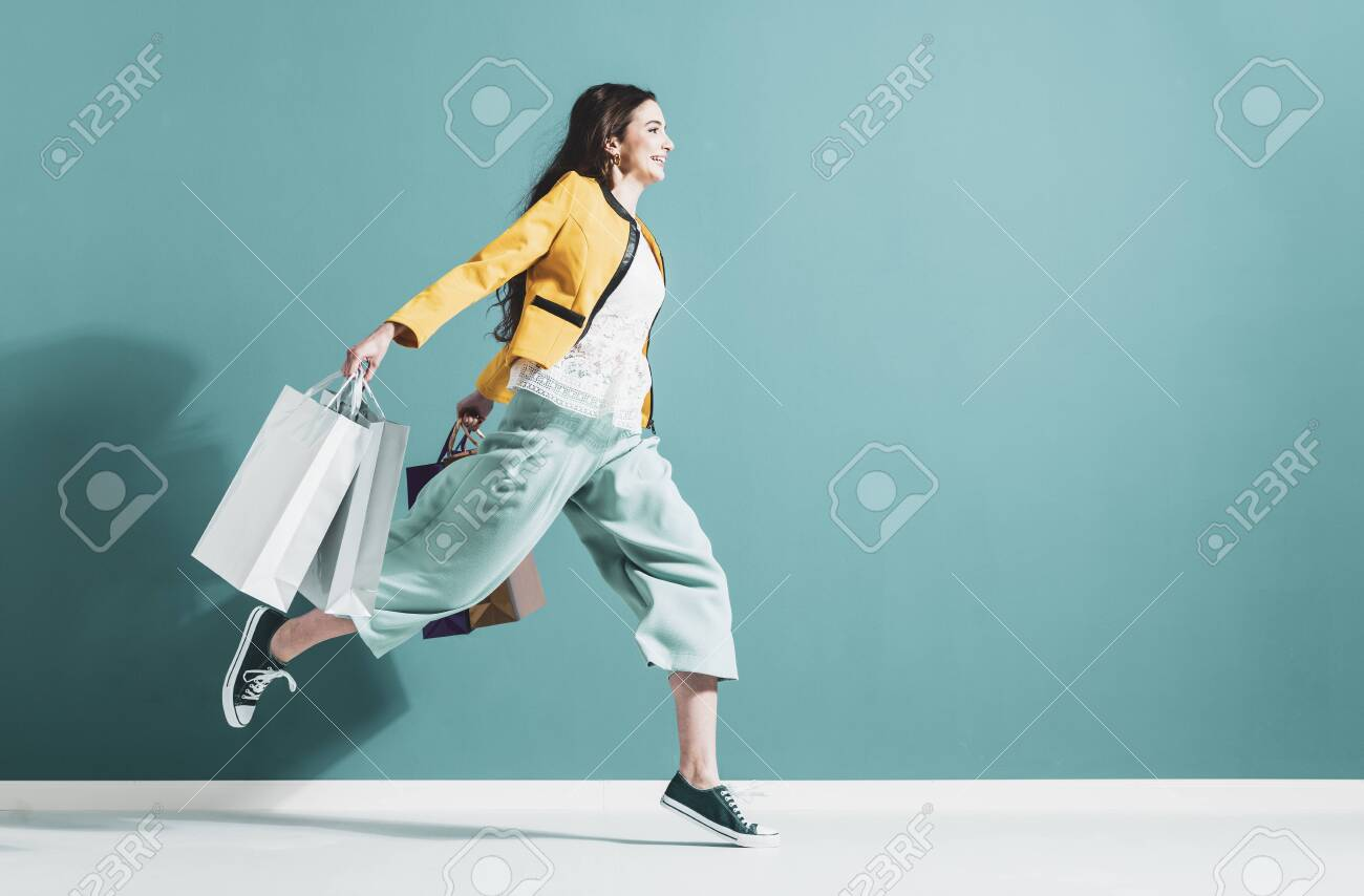 Cheerful happy woman enjoying shopping: she is carrying shopping bags and running to get the latest offers at the shopping center - 125391249