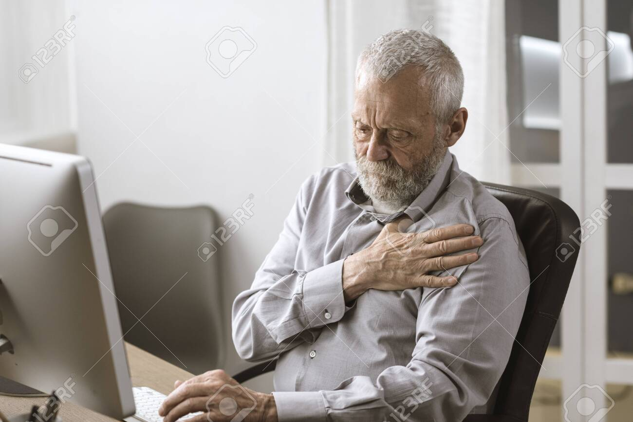 Concerned senior man having an heart attack, he is sitting at desk and touching his chest - 125897028