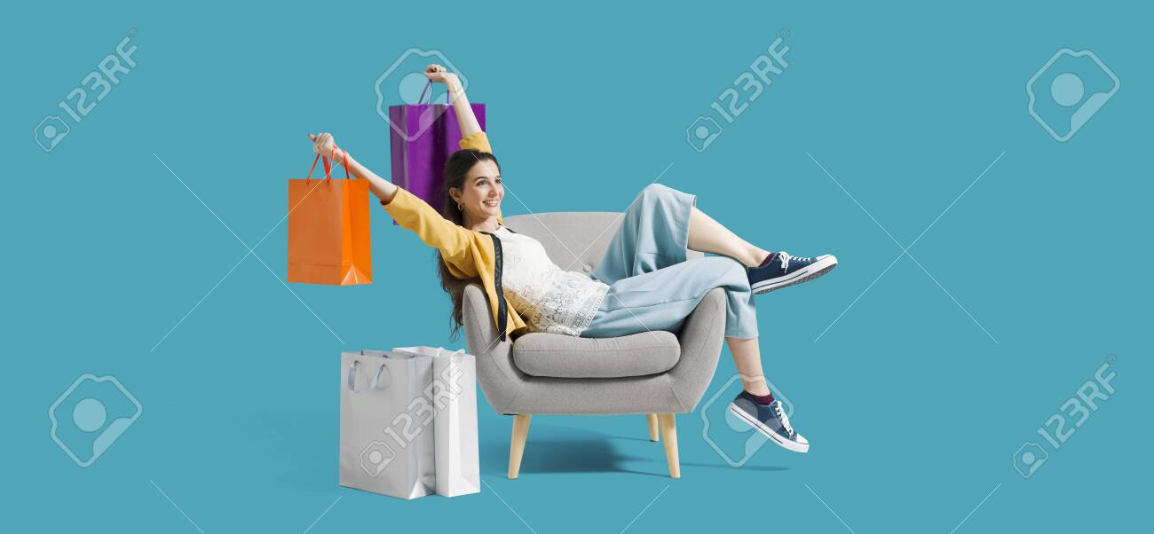 Cheerful happy shopaholic woman with lots of shopping bags, she is sitting on an armchair and celebrating with arms raised - 130088920