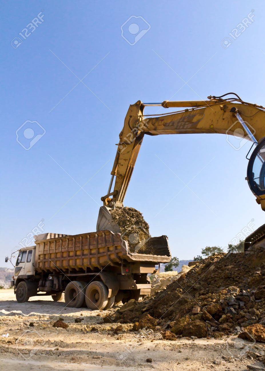 The dredge and the dumper truck work on building. Stock Photo - 12530898