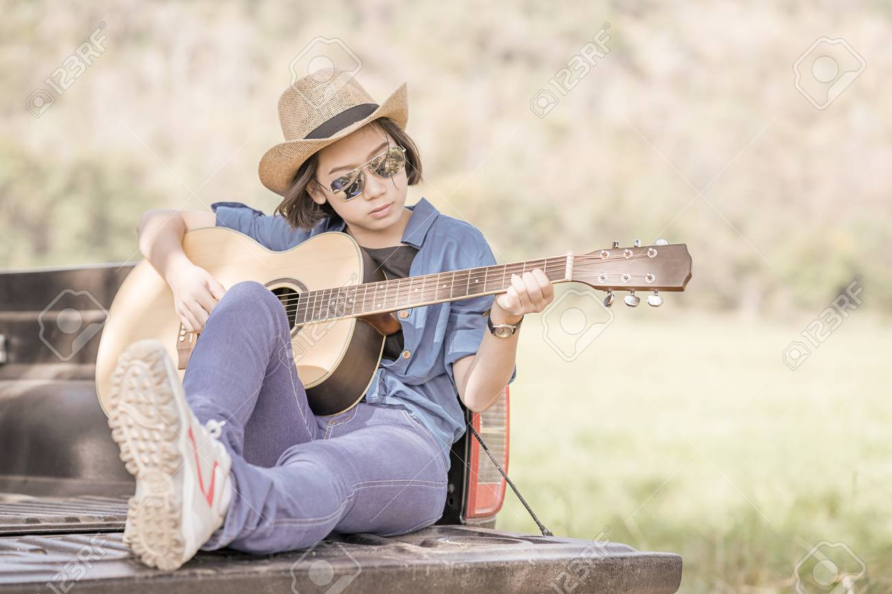 ea216aad71fe1 Stock Photo - Young asian women short hair wear hat and sunglasses playing  guitar