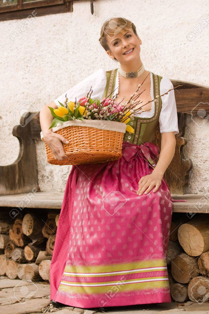 Bavarian girl sitting on a bench in dress and bouquet of Easter basket Stock Photo - 12944100
