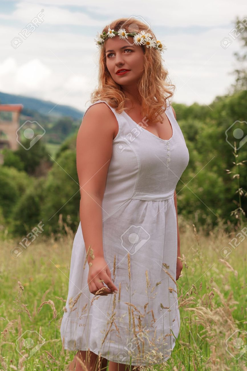 Young blond plus-size model with flower wreath in her hair and white dress standing in tall grass Stock Photo - 21509046